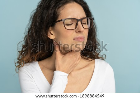Woman having sore throat, tonsillitis, feeling sick, suffering from painful swallowing, angina, strong pain in throat, loss of voice, holding hand on her neck, isolated on studio blue background. Stock photo ©