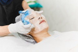 Woman having stimulating facial treatment at professional clinic