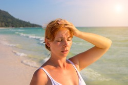 Woman having sun stroke on sunny beach. Woman on hot beach with sunstroke. Health problem on holiday. Medicine on vacation. Dangerous sun. Beach life. Sunstroke on sunny beach. Healthcare in tropics
