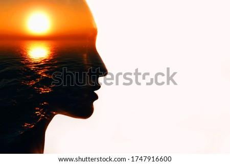 Photo of Woman head silhouette with sun inside with copy space. Multiple exposure image.