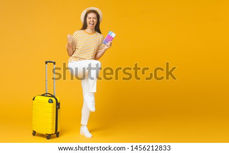 Woman heading for vacation feeling joy of cheap travel tickets, isolated, copyspace included