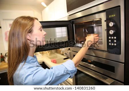 Woman heating dish in microwave #140831260