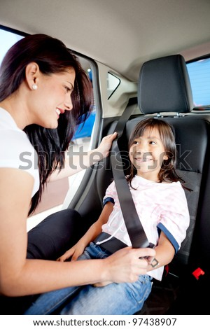 Woman helping a girl to fasten her seat belt in a car