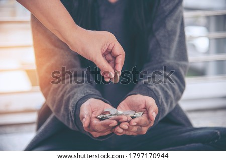 Woman helping hands to homeless people poverty beggar man holding hands asking for money job and hoping help in helpless dirty city sitting on streets. Desperate Beggar in city concept. Foto stock ©