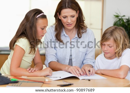 Woman helping her children with homework