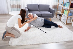 Woman Helping Her Father After Falling On Carpet At Home