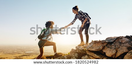 Woman helping her friend to climb the cliff and reach the top of mountain. Friends helping each other during hiking a mountain.