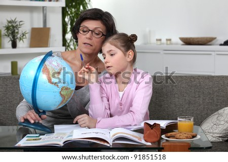 Woman helping her granddaughter complete her geography homework