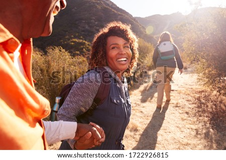 Woman Helping Man On Trail As Group Of Senior Friends Go Hiking In Countryside Together Stockfoto ©