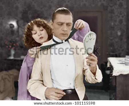 Woman helping man tie bow tie