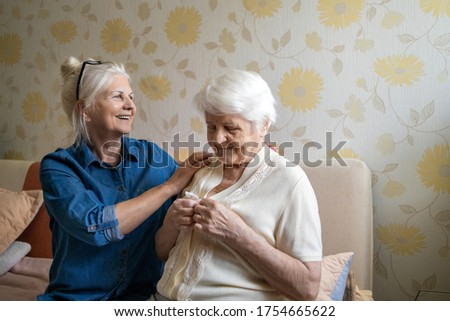 Woman helping senior woman dress in her bedroom  Photo stock ©