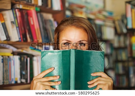 Woman hiding behind the green book