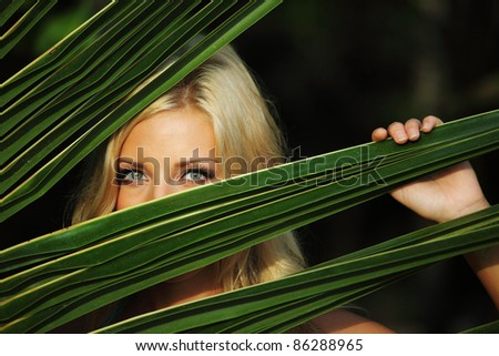 woman hiding behind the palm leaves