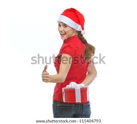 Woman hiding Christmas present behind back and showing thumbs up