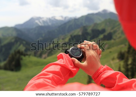 Woman hiker checking the altimeter