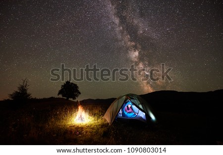 Woman hiker having a rest at night camping beside campfire in the mountains under incredible beautiful starry sky and Milky way. Girl sitting inside illuminated tent and sleeping bag. Astrophotography #1090803014