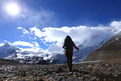 Woman hiker hiking in winter high altitude mountains