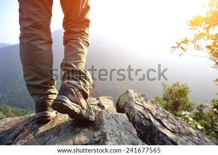woman hiker legs stand on mountain top cliff edge