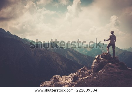 Woman hiker on a top of a mountain  - Shutterstock ID 221809534