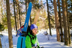 Woman hiker on the trail in winter mountains with skis on the backpack