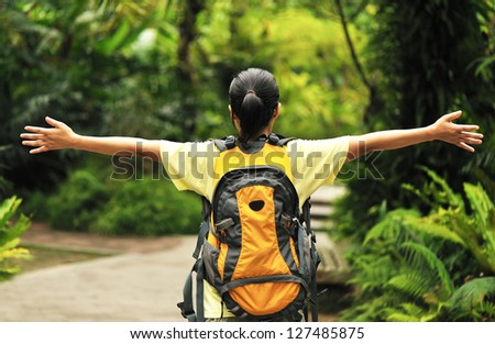 woman hiker open arms in tropical forest