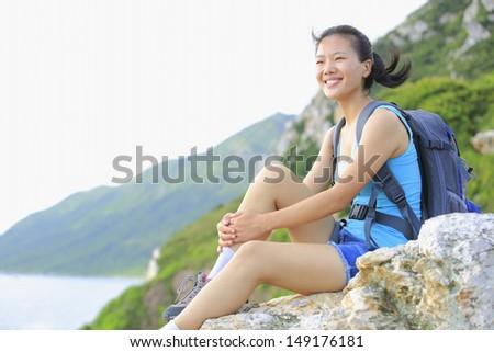 woman hiker smile/sit on seaside mountain rock