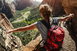 Woman hiker standing with raised hands and watching valley view of Zion National Park, USA