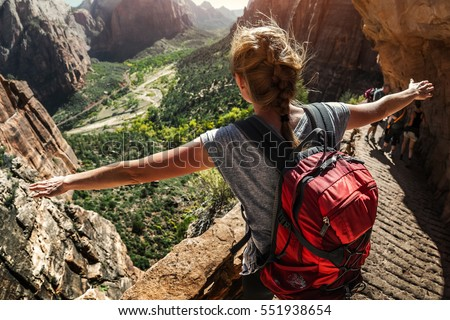 Woman hiker standing with raised hands and watching valley view of Zion National Park, USA #551938654