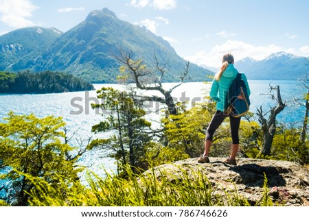 Woman hiker stands on the coast of the lake and enjoys mountain view. Lake district of Argentina