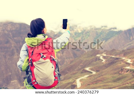 woman hiker taking photo at nujiang river 72 turn road, tibet,china