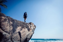 Woman hiker walking on seaside rock cliff edge