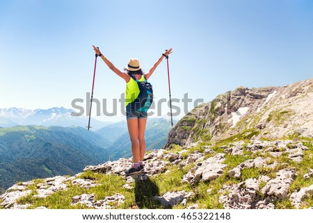 woman hiker with trekking poles is enjoying the view from the mountains in the hat #465322148
