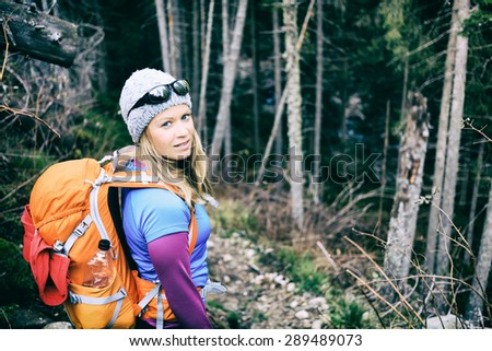 Woman hiking and camping on trail in winter dark dry forest. Recreation and healthy fitness lifestyle outdoors in inspirational nature. Beauty blond hiker camp with backpack looking at camera.