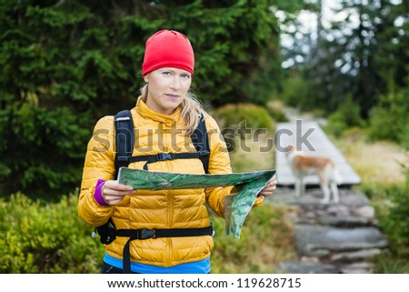 Woman hiking and reading map in forest, hiker with dog, Karkonosze Mountains in Poland