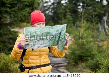 Woman hiking and reading map in forest, Karkonosze Mountains in Poland, Trekking in autumn nature, outdoors exercising.