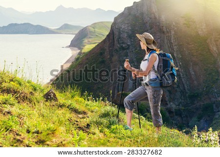 Woman hiking. Hike in the mountains. Woman traveler with backpack on beautiful summer landscape.