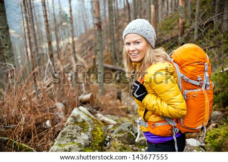 Woman hiking in autumn forest in mountains. Recreation and healthy lifestyle outdoors in nature. Beauty blond looking at camera smiling.