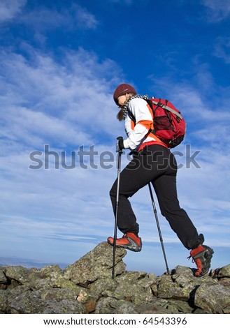 Woman hiking in Autumn mountains, nordic walking and backpacking. - stock photo