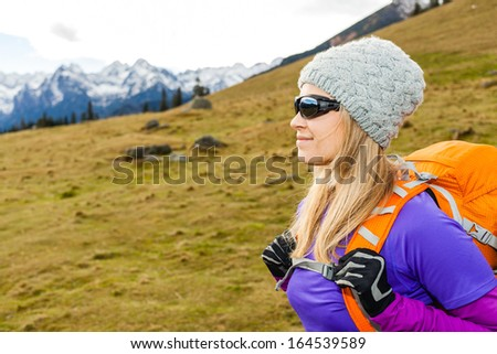 Woman hiking in beautiful mountains with backpack. Recreation and healthy lifestyle outdoors in nature. Beauty blond hiker looking at mountain view on sunset.