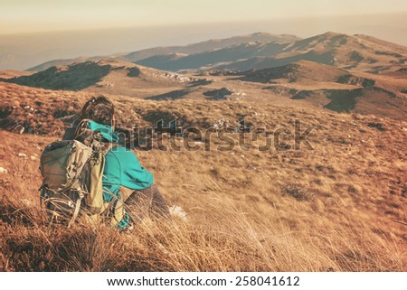 Woman hiking in beautiful nature, recreation and healthy lifestyle outdoors in wild. Hiker backpacker sitting on mountain top.
