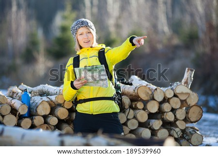 Woman hiking in forest reading map. Recreation and healthy lifestyle outdoors in nature. Beauty blond looking at camera on sunset.