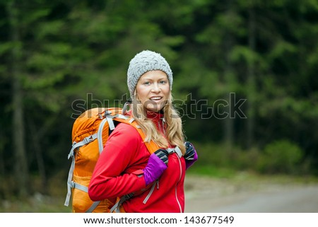Woman hiking in forest. Recreation and healthy lifestyle outdoors in nature. Beauty blond hiker walking with backpack looking at camera.