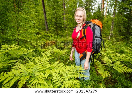 Woman hiking in summer forest. Recreation and healthy lifestyle outdoors in nature. Beauty blond looking at camera smiling.