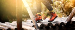 Woman hiking in the mountain. View of hiking boots on wooden bridge in the forest.