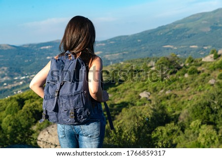 Woman hiking in the mountains at a tourist spot looking at the views