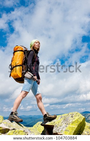 Woman hiking in the mountains, walking and backpacking