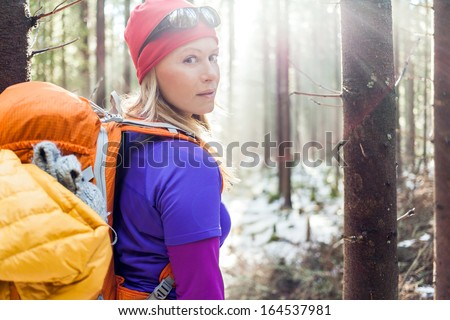 Woman Hiking In White Winter Forest, Backlight By Morning Sunlight Rays, Recreation And Healthy Lifestyle Outdoors In Nature. Beauty Blond Hiker Backpacker Looking At Camera On Sunset.