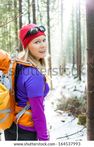 Woman hiking in white winter forest, backlit by morning sunlight rays, recreation and healthy lifestyle outdoors in nature. Beauty blond hiker backpacker looking at camera on sunrise.