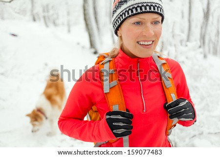 Woman hiking in white winter forest with dog akita inu. Recreation and healthy lifestyle outdoors in nature. Beauty blond hiker walking on snowy footpath.