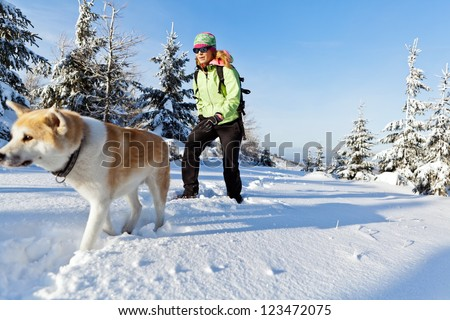 Woman hiking in winter mountains with akita dog, walking on white snow. Sport and fitness in wilderness nature outdoors. Beautiful female hiker with canine.